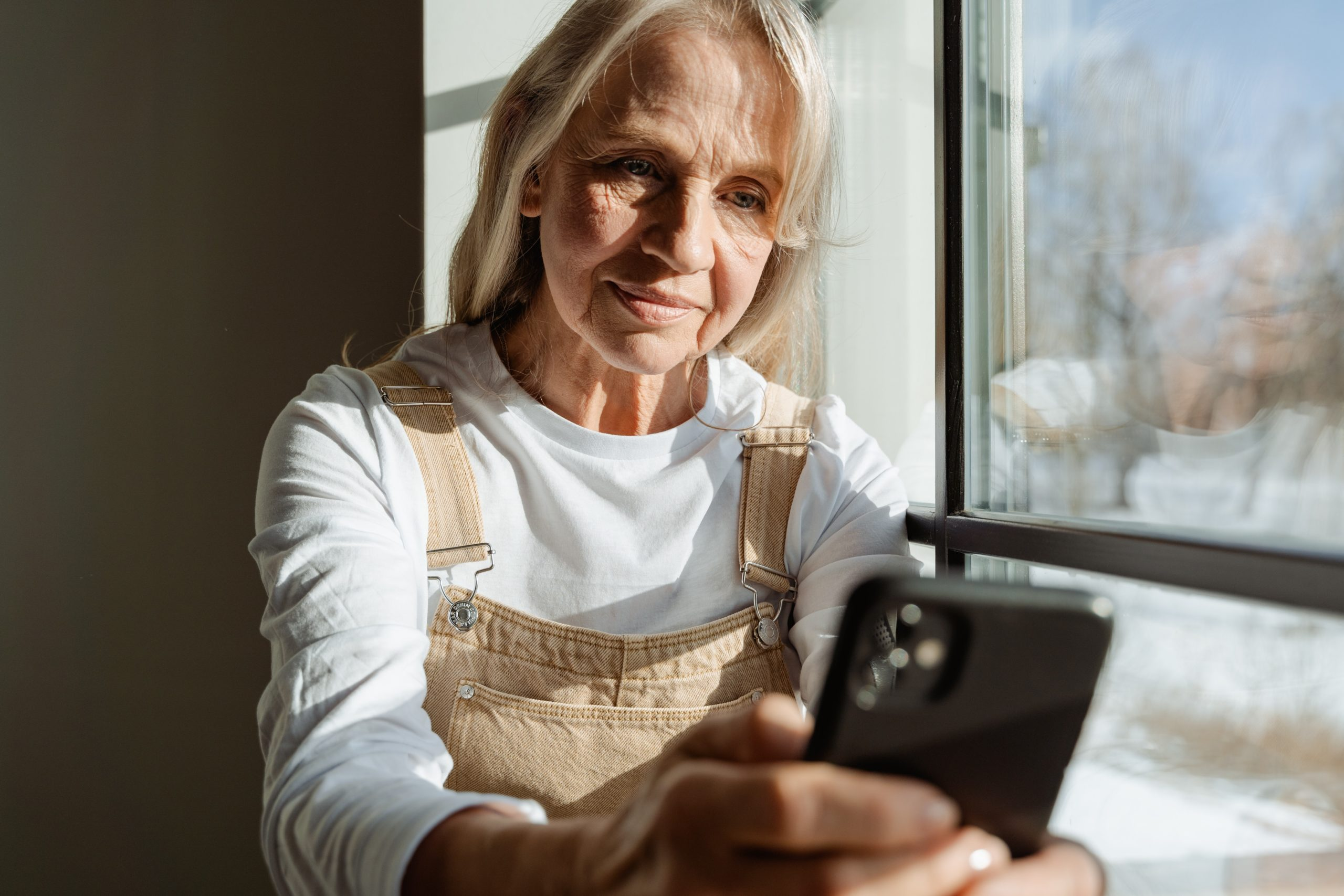 Older woman looking at her phone by the window